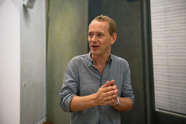 Christian Jankowski vor seinem Kulissenbild mit dem Kölner Hotelzimmer, in dem Martin Kipenberger wohnte. Foto: Lena Ganssmann
