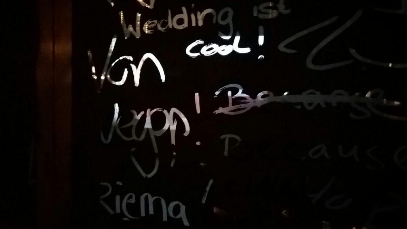 Galerie Wedding: Passanten und Obdachlose haben Gedichte und Sprüche in die schwarze Fensterfarbe geschrieben. Die Scheinwerfer der Autos auf der Müllerstraße werfen durch die Schrift bewegte Ornamente auf den Galerieboden