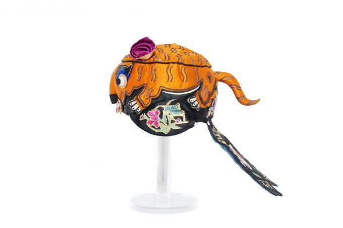 Textil mit Seidenfädenstickerei und Applikationen (u.a. Goldfolie)Tiermützen gehören in China zur traditionellen Bekleidung kleiner Kinder. Die Stärke der Tiere überträgt sich auf das Kind – so schützt die Mütze nicht nur vor Sonne und Kälte.Foto: Ethnologisches Museum – Staatliche Museen zu Berlin