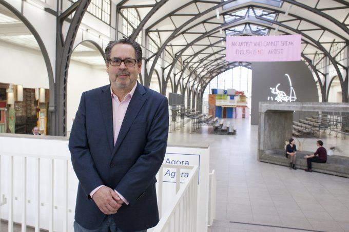 Direktor Udo Kittelmann in der Haupthalle des Hamburger Bahnhofs.  Das rosa Banner ist vion Mladen Stilinovic und sagt: