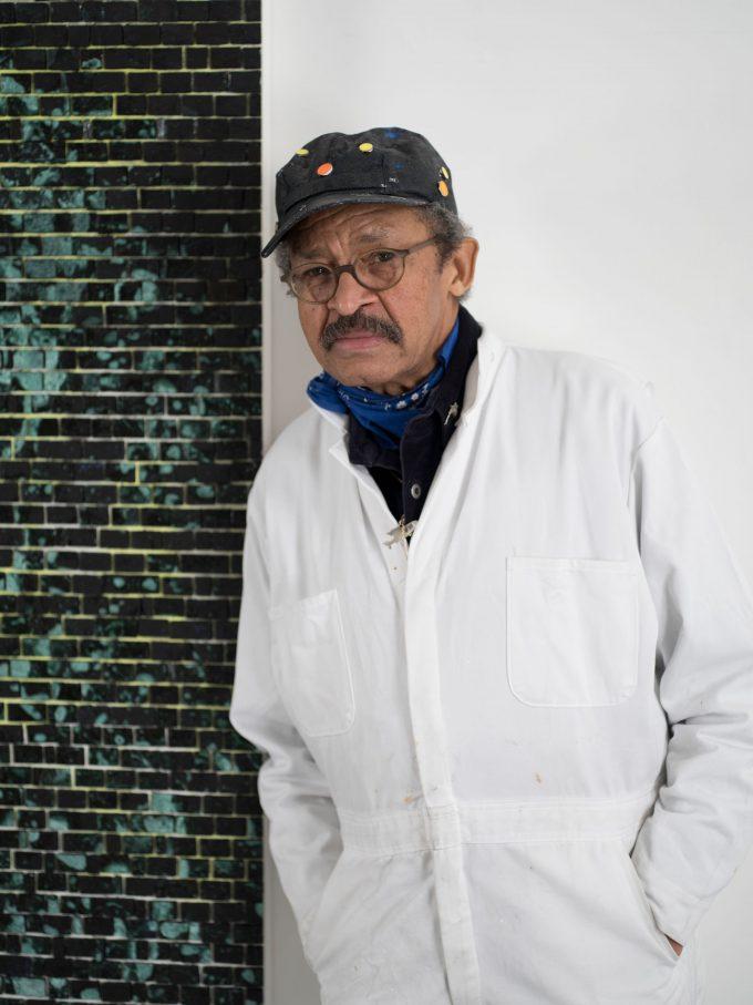 Porträt Jack Whitten im Malerkittel neben einem Bild aus Farbsteinchen, von John_Berens