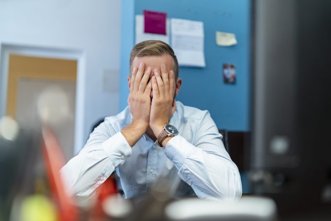 Businessman sitting at desk in office with hands covering face model released Symbolfoto property released PUBLICATIONxINxGERxSUIxAUTxHUNxONLY DIGF08004
